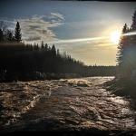 The river runs past the setting sun
